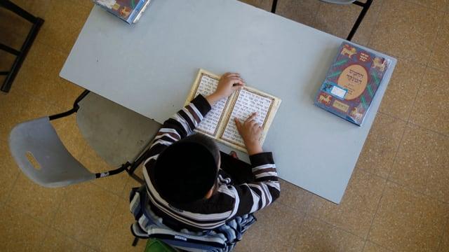 Ein jüdischer Schüler mit einer Kippa sitzt in der Schulbank.