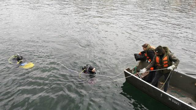 Zwei Taucher im Wasser, zwei Jugendliche mit Schwimmwesten im Weidling