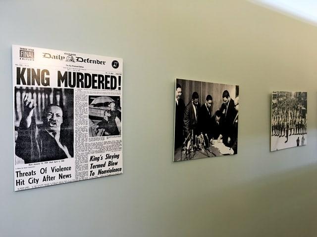 Eine Wand mit Fotos und Zeitungsartikeln.