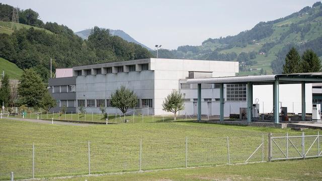 Industriegebäude mit einer Wiese davor und einem Zaun drum herum.
