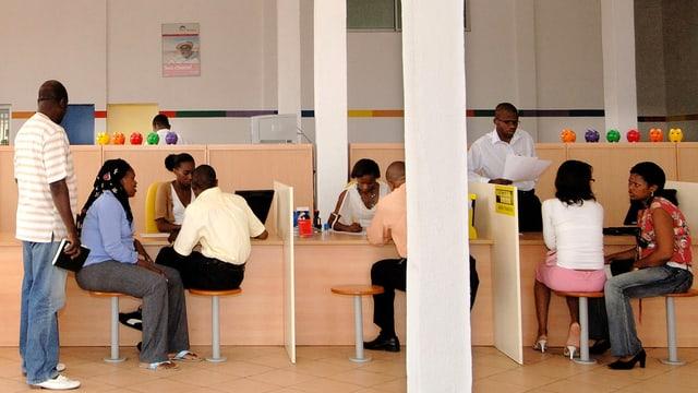 Menschen sitzen an den Schaltern einer Mikrokredit-Bank in Angola.
