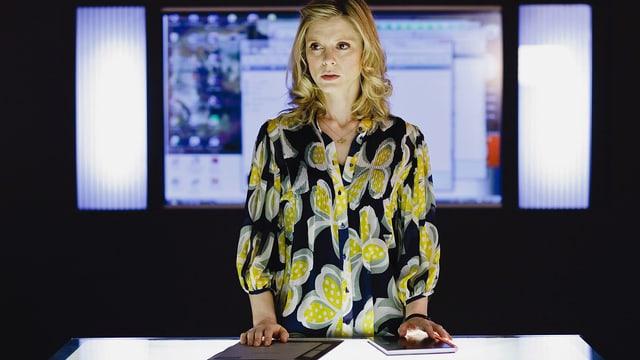 Eine Frau vor einem riesigen Computerbildschirm.
