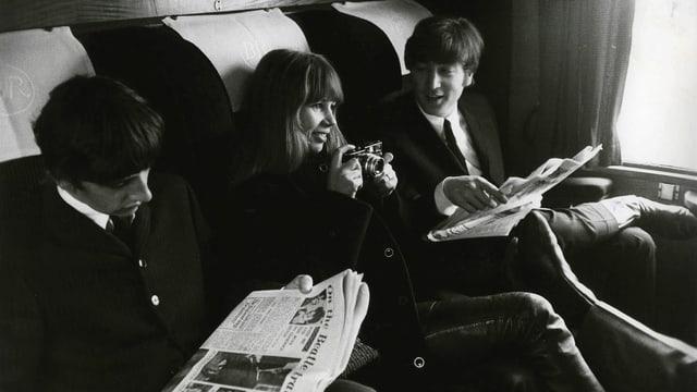 Astrid Kirchherr neben Ringo Starr und John Lennon in einem Zugabteil.