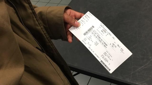 Eine Person hält ein Ticket in den Händen.