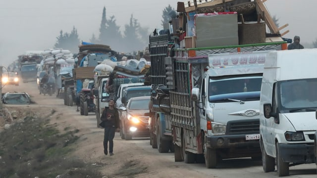 Kolonne mit Autos, Transportern und LKWs, alle voll beladen mit Möbeln und Haushaltswaren.
