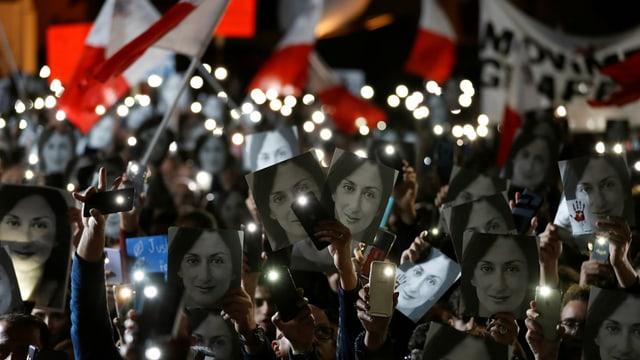 Demonstranten bei Nacht, viele tragen ein Foto der ermordeten Journalistin Daphne Caruana Galizia.