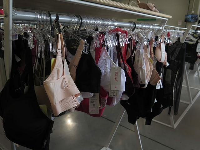 An einer Kleiderstange in einem Laden hängen Marken-BHs.