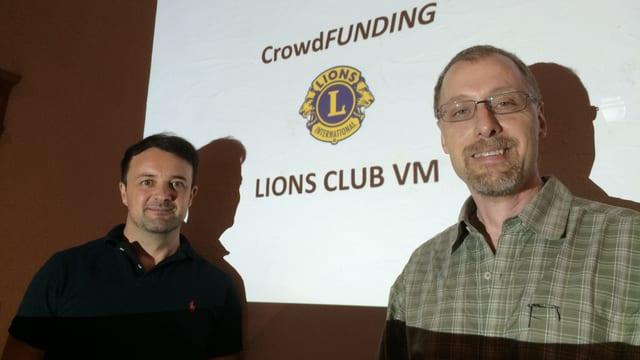 Patrick Wegmann e Plinio Meyer davant in screen cun si il logo dal Club da liuns.