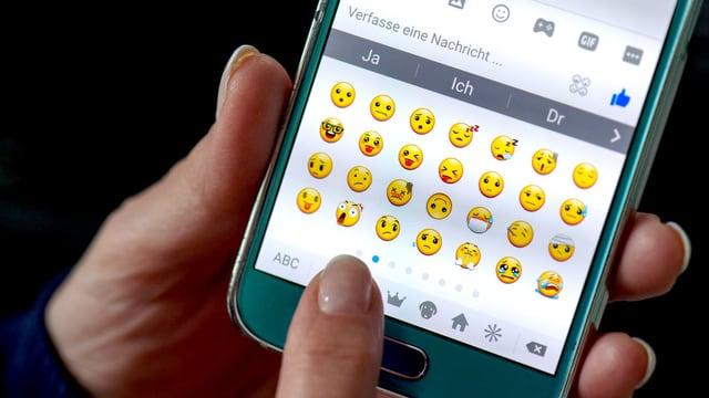 Eine Hand tippt Emojis auf einem Smartphone-Display.