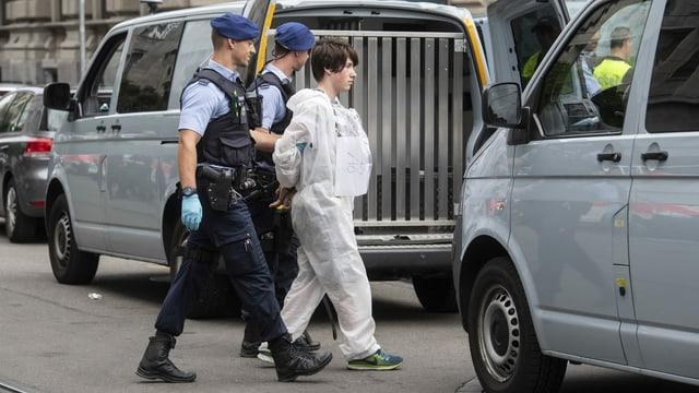 Polizisten führen einen Klimaaktivisten ab, der zuvor beim Eingang der Bank Credit Suisse demonstriert hatte.