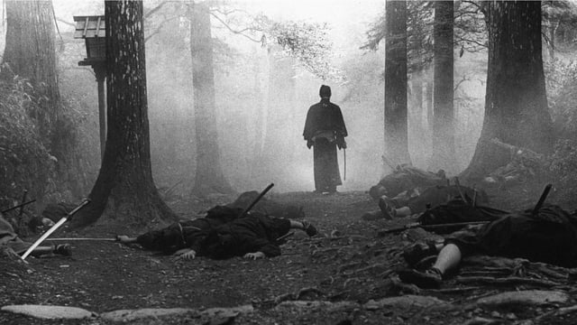 Ein Mann mit Schwert in einem Wald. Vor ihm liegen mehrere Personen am Boden