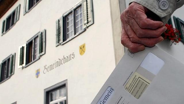 Maun d'in um velg cun busta da votaziun e davostiers la chasa communala da Grüsch.