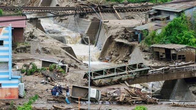 Schlamm, Schutt und eine weggespülte Brücke in Japan.
