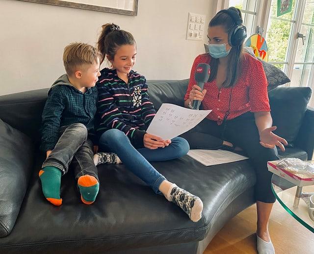 Matteo, Julia und Angela sitzen auf dem Sofa