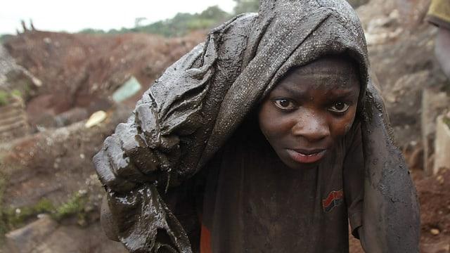 Ein Junge blickt in die Kamera, er trägt einen Schlammverschmierten Sack auf dem Rücken.