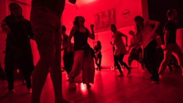 Menschen tanzen in einem rot beleuchteten Raum