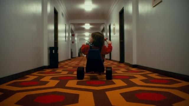 Danny fährt mit seinem Dreirad einen Flur des Overlook-Hotels herunter - wie in «The Shining».