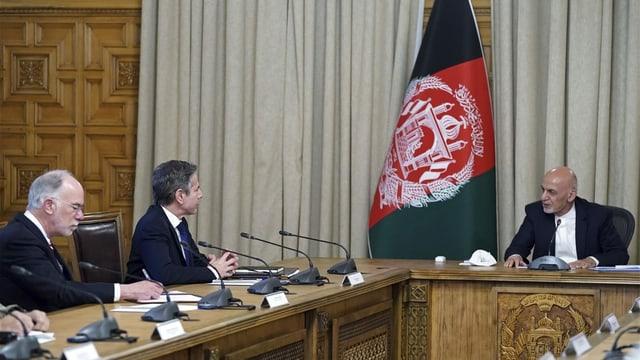 Drei Männer in Anzügen sitzen an einem Tisch und sprechen miteinander.