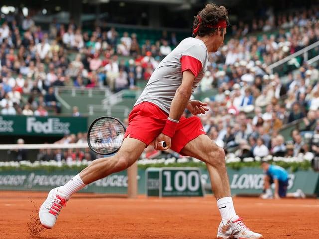 Roger Federer schlägt einen Tweener.