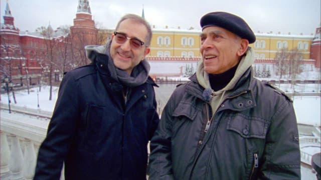 Filmstill: Der schweizerisch-irakische Regisseur Samir neben einem Mann mit Béret.