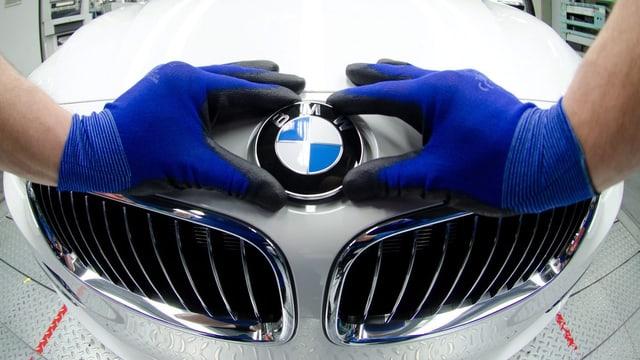 Ein Mitarbeiter von BMW montiert mit Handschuhen das Logo auf der Kühlerhaube.