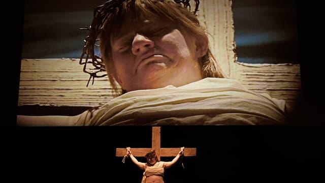 Theaterszene: Eine behinderte Frau hängt am Kreuz.