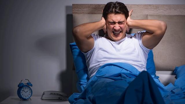 Mann sitzt im Bett und hält sich genervt die Ohren zu.