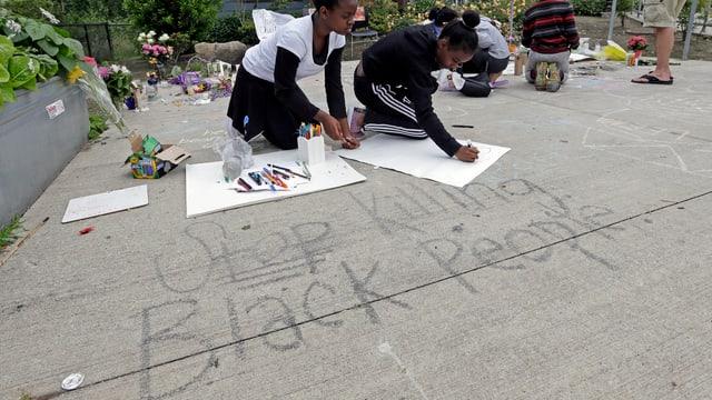 Mädchen, die auf dem Boden Plakate beschriften.