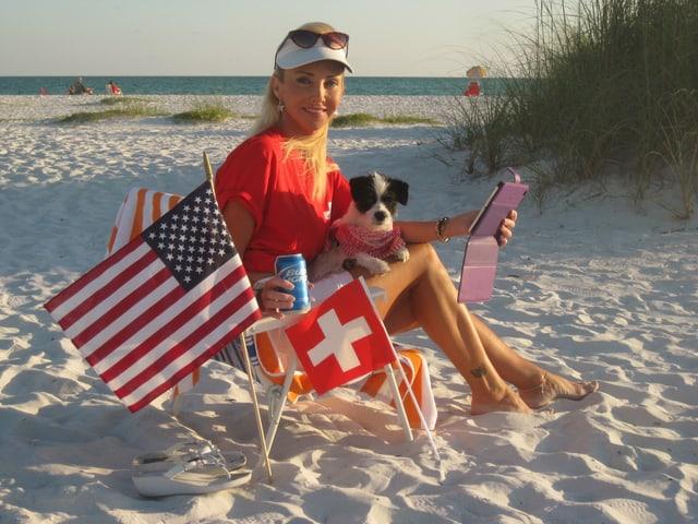 Marianne Siegler auf einem Stuhl im Strand mit Hund auf der Schoss und Tablet in der Hand. Vor ihr stecken zwei Fähnchen im Sand: ein Schweizer-Fähnchen und eine USA-Flagge.