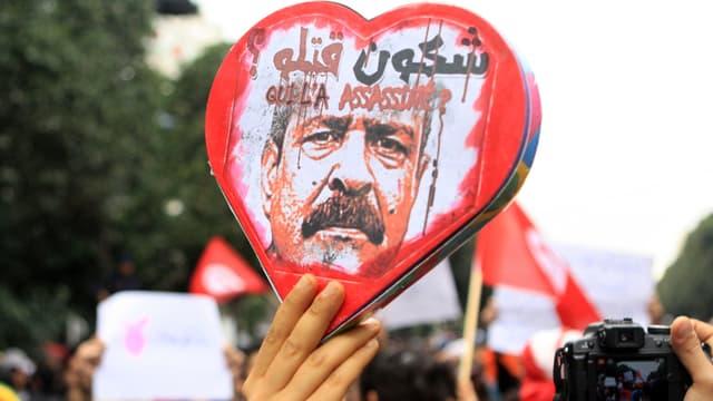 Ein Demonstrant hält ein Herz mit dem Konterfei Belaïds empor.