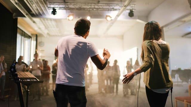 Ein Mann und eine Frau auf der Bühne. Sie sind gegen ein Publikum gerichtet.