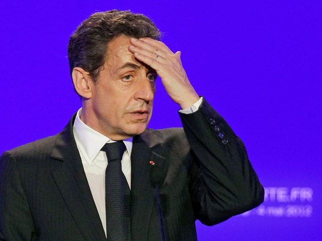 Nicolas Sarkozy wischt sich Schweiss von der Stirne.