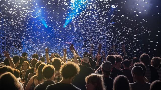 Personen feiern vor einer Musikbühne.