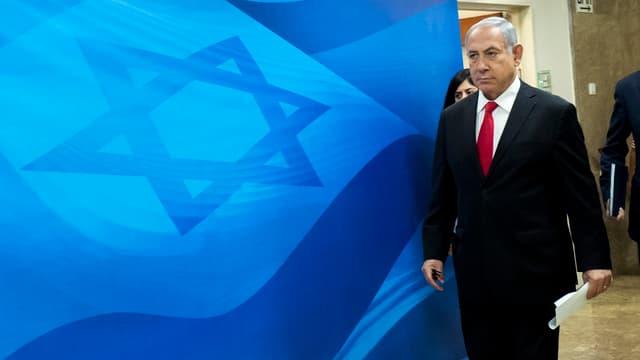 Netanjahu geht vor einer blauen Israel-Flagge vorbei.
