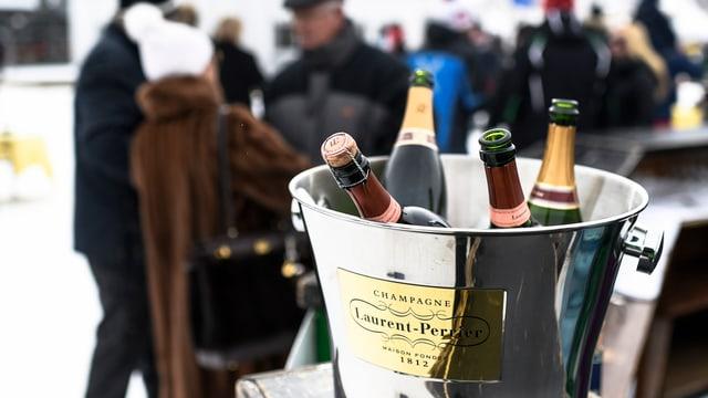 Champagnerflaschen in einem silbernen Eimer, Menschen im Hintergrund