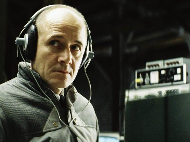 Ein Mann trägt Kopfhörer und blickt kritisch nach links.
