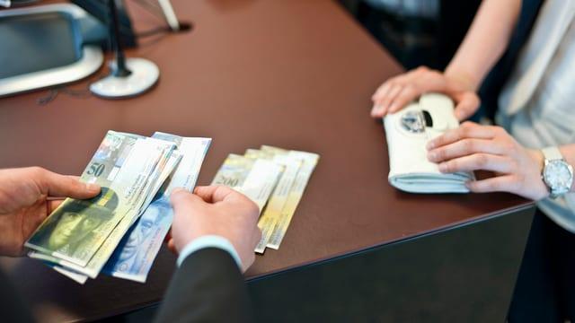 Eine Hand zahlt an einem Bankschalter Geld aus.
