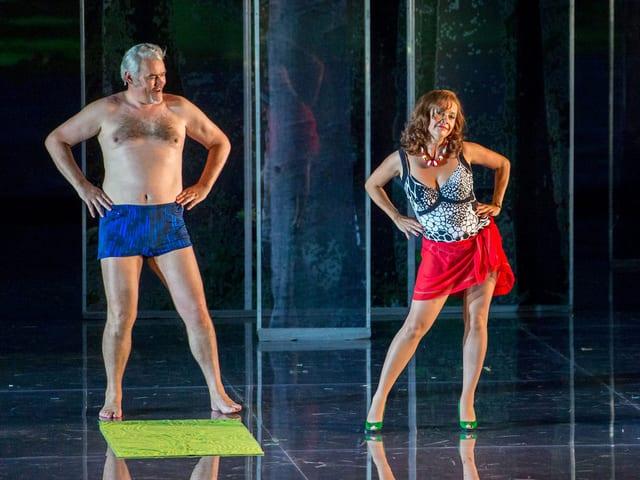 Albert Pasendorfer und Angelika Kirchschlager stehen in Badekleidung auf der Bühne, neben ihnen Strandtuch und Badetasche.