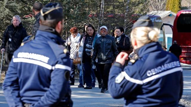 Angehörige auf dem Weg, im Vordergrund zwei Gendarmen.