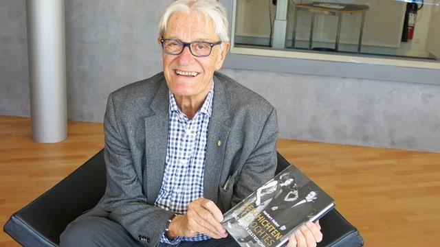 Ein alter Mann mit einem Buch in der Hand.