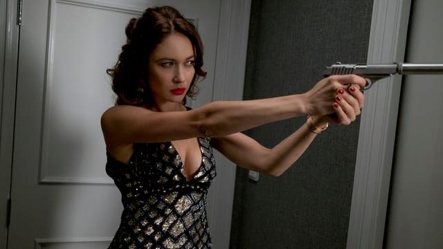Auf dem Foto ist die russische Spionin Ophelia (Olga Kurylenko) mit einer Pistole zu sehen.