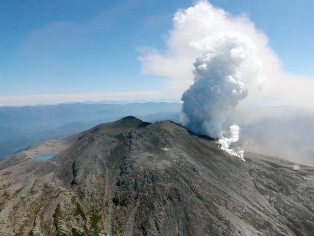 Der rauchende Vulkan Ontake aus der Ferne fotografiert vor blauem Himmel