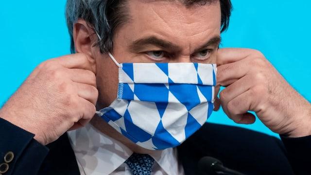 Markus Söder zieht sich eine Hygienemaske an