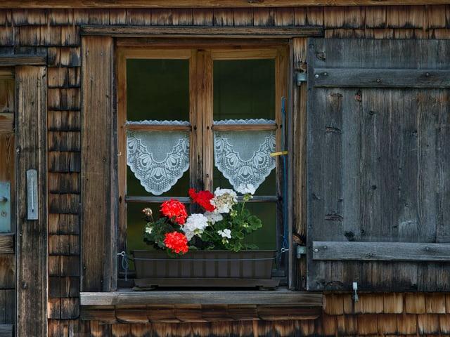 Holzhaus mit einem Geraniumkistchen vor dem Fenster.