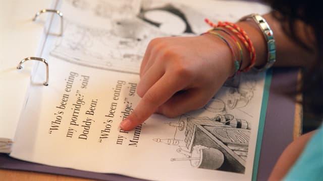 Schülerin zeigt mit Finger auf eine englische Textpassage in ihrem Lernordner