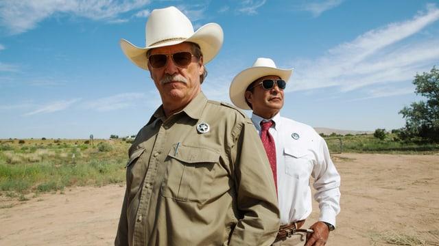Zwei Ranger mit Hut in der kargen Landschaft.