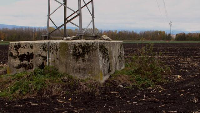 Abgesunkener Boden um das Fundament eines Strommasts