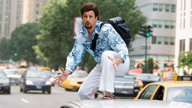 Ein Mann steht auf dem Dach eines fahrenden Autos.