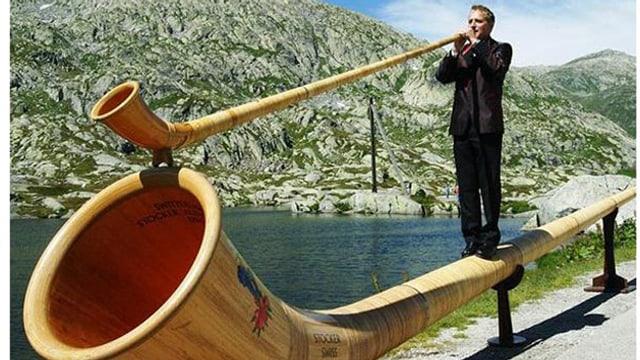 Walti Sigrist mit herkömmlichem Alphorn auf seinem Riesenalphorn stehend.