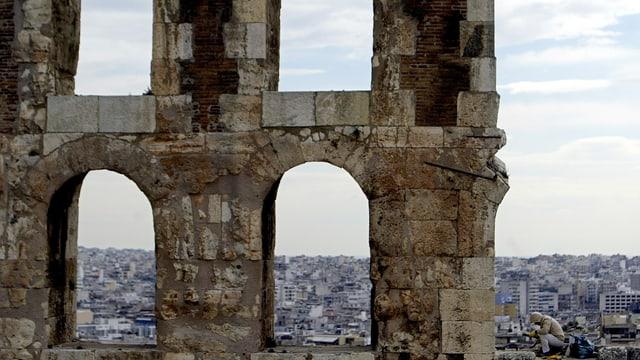 Blick durch die Akropolis auf Athen. Ein Mann sitzt daneben, arbeitend.